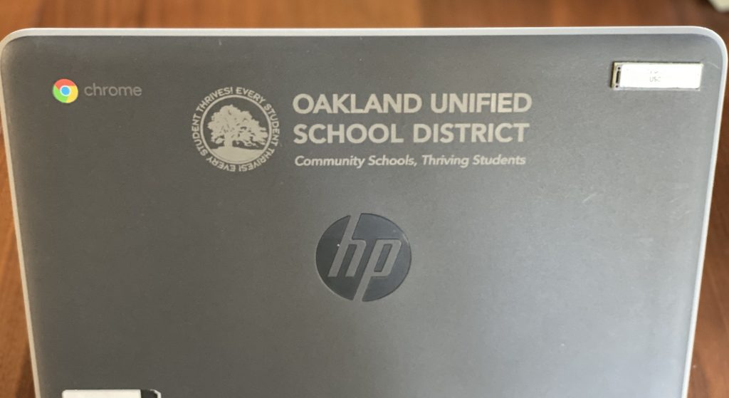An image of a grey Chromebook laptop with OUSD engraved on it.