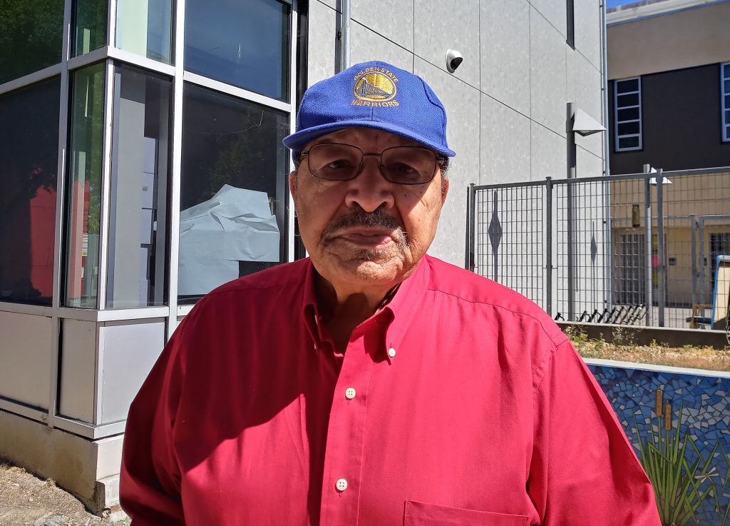 Ben Tapscott. Photo by Tony Daquipa. A man wearing a blue hat and red shirt looks at camera.