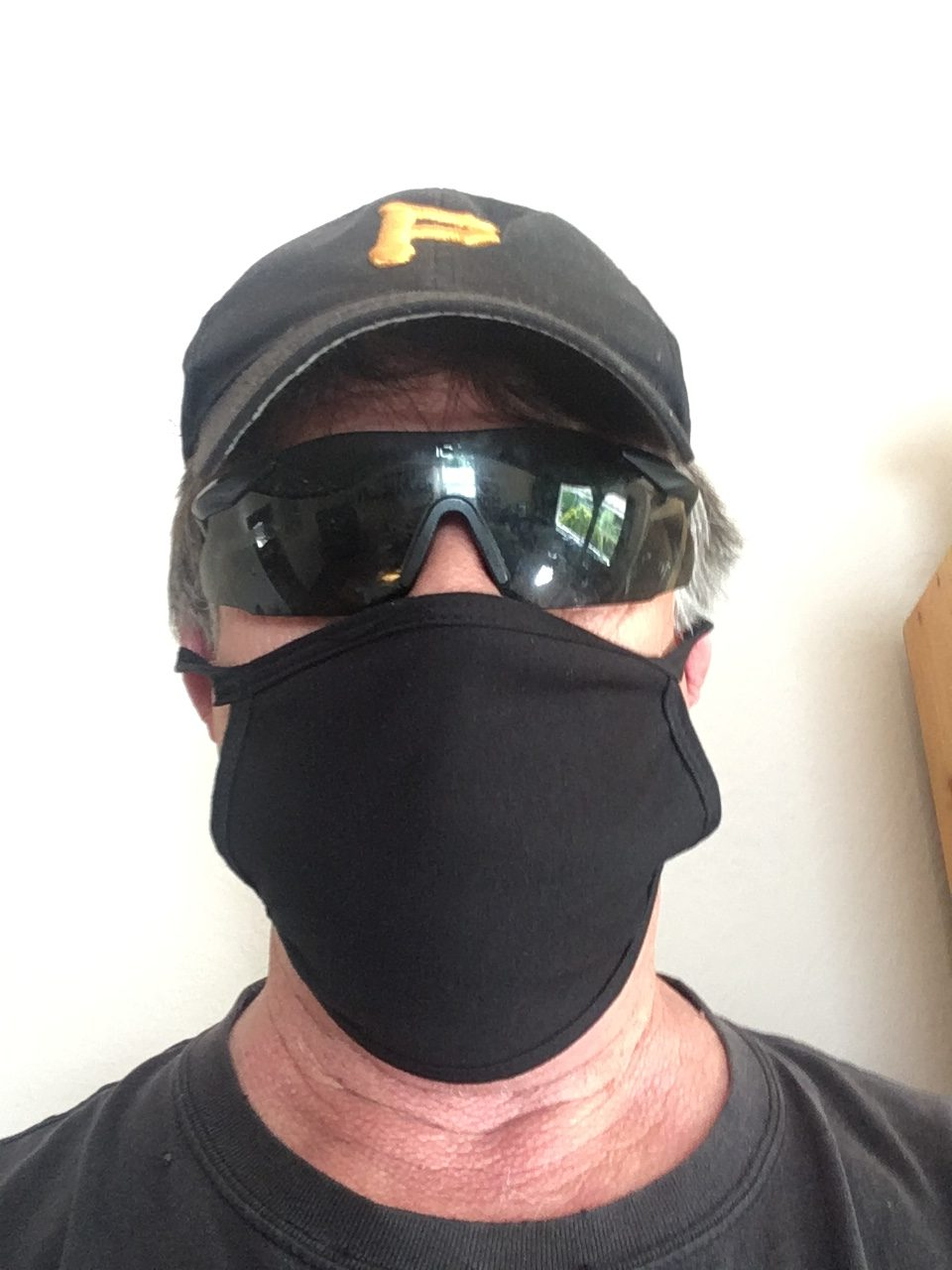 A man wears a cap, glasses, and a black mask