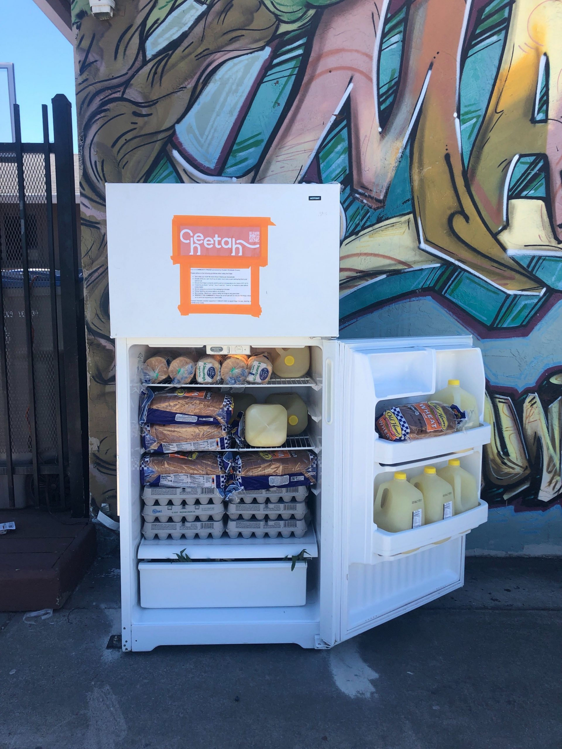 "An open small refrigerator door with ""Cheetah"" in orange logo. The fridge has bread, juice, and eggs."