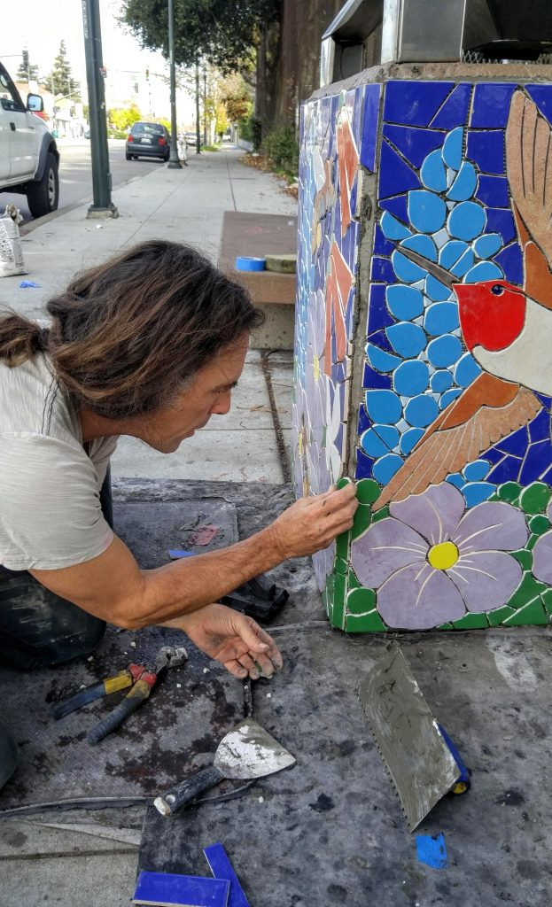 A male artist in a ponytail puts on mosaics on a trash can in Oakland.