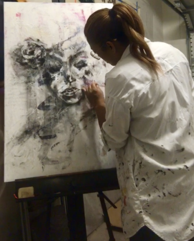 an artist in a ponytail works on a black and white drawing.