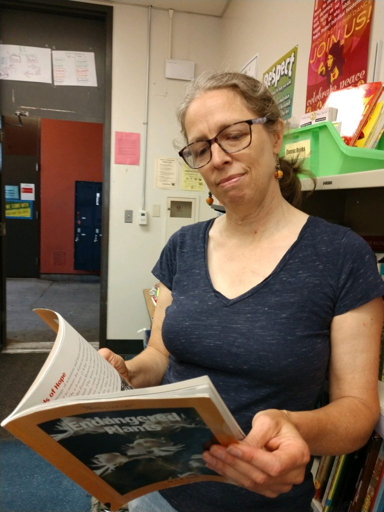 A woman with glasses is reading a book.