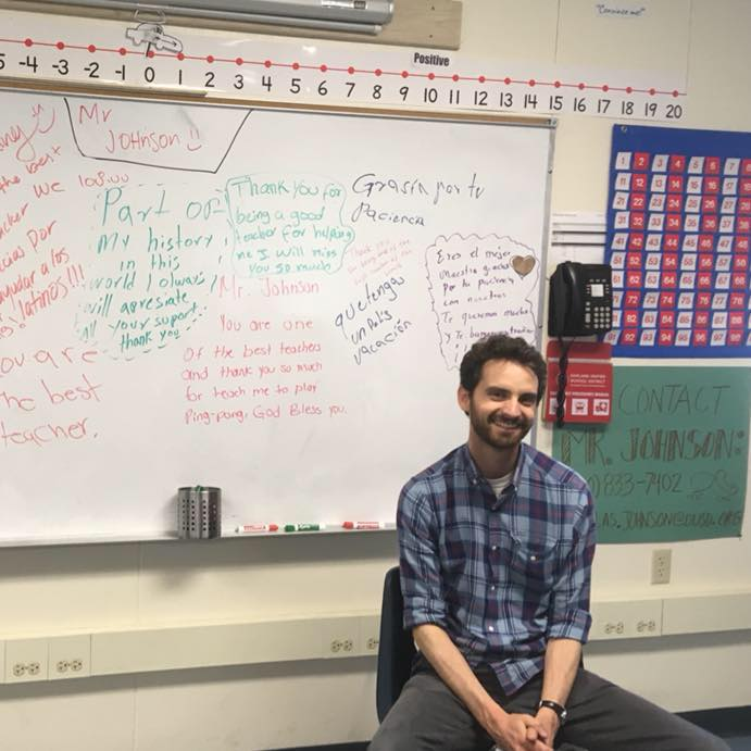 A teacher sits in a chair in front of a whiteboard.