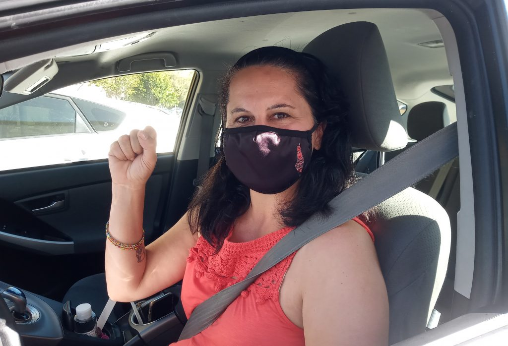 Noura Khouri. A woran wearing a facemask and her fist up sitting inside her car.