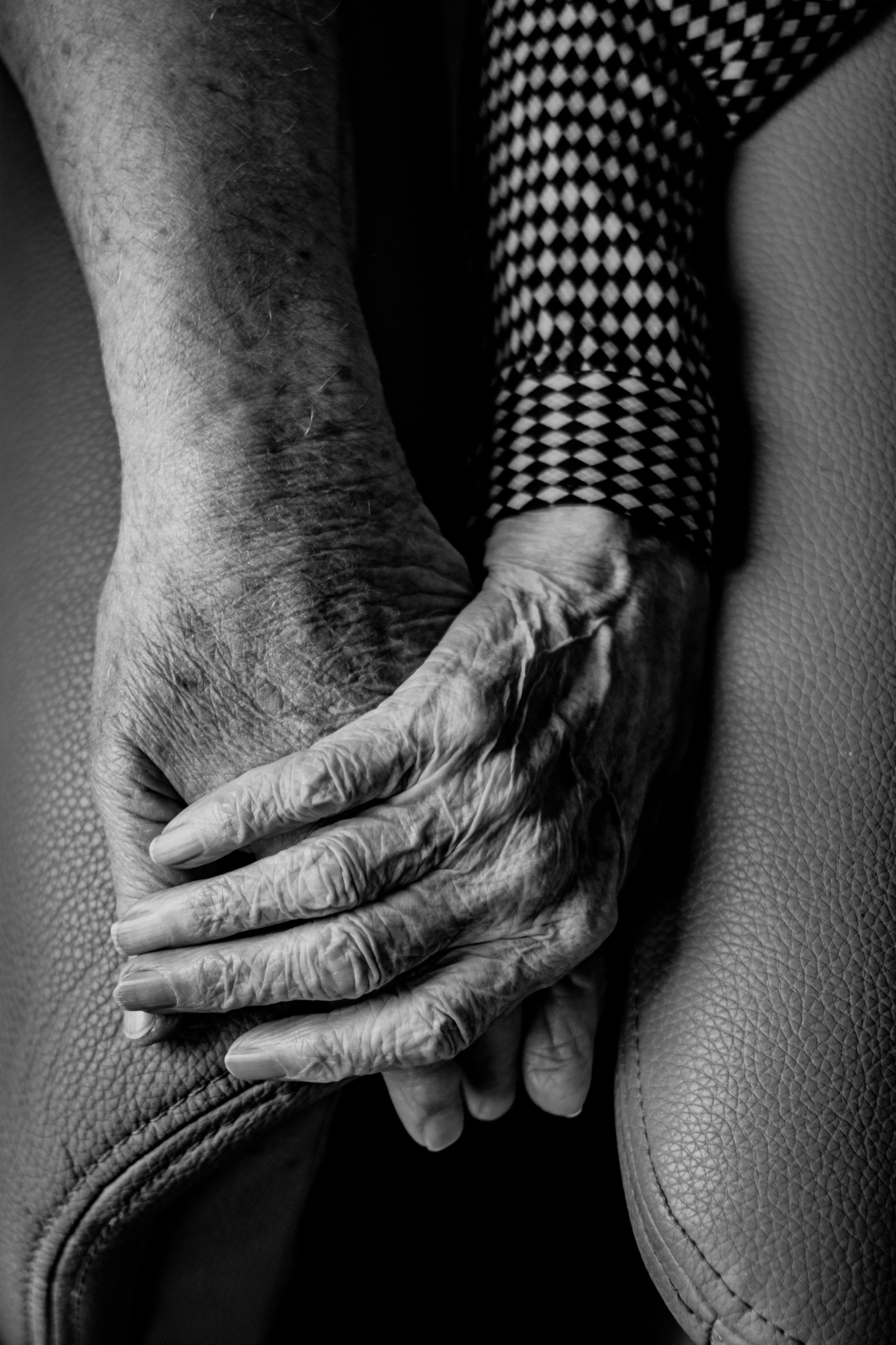 A black and white photo of older people holding hands.