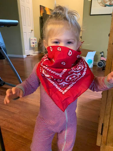 A toddler wears a red bandana as a mask.