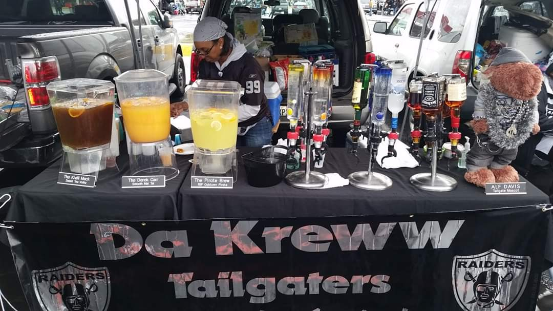 """A close up photo of a makeshift tailgating bar with """"Da Kreww"""" banner in front."""