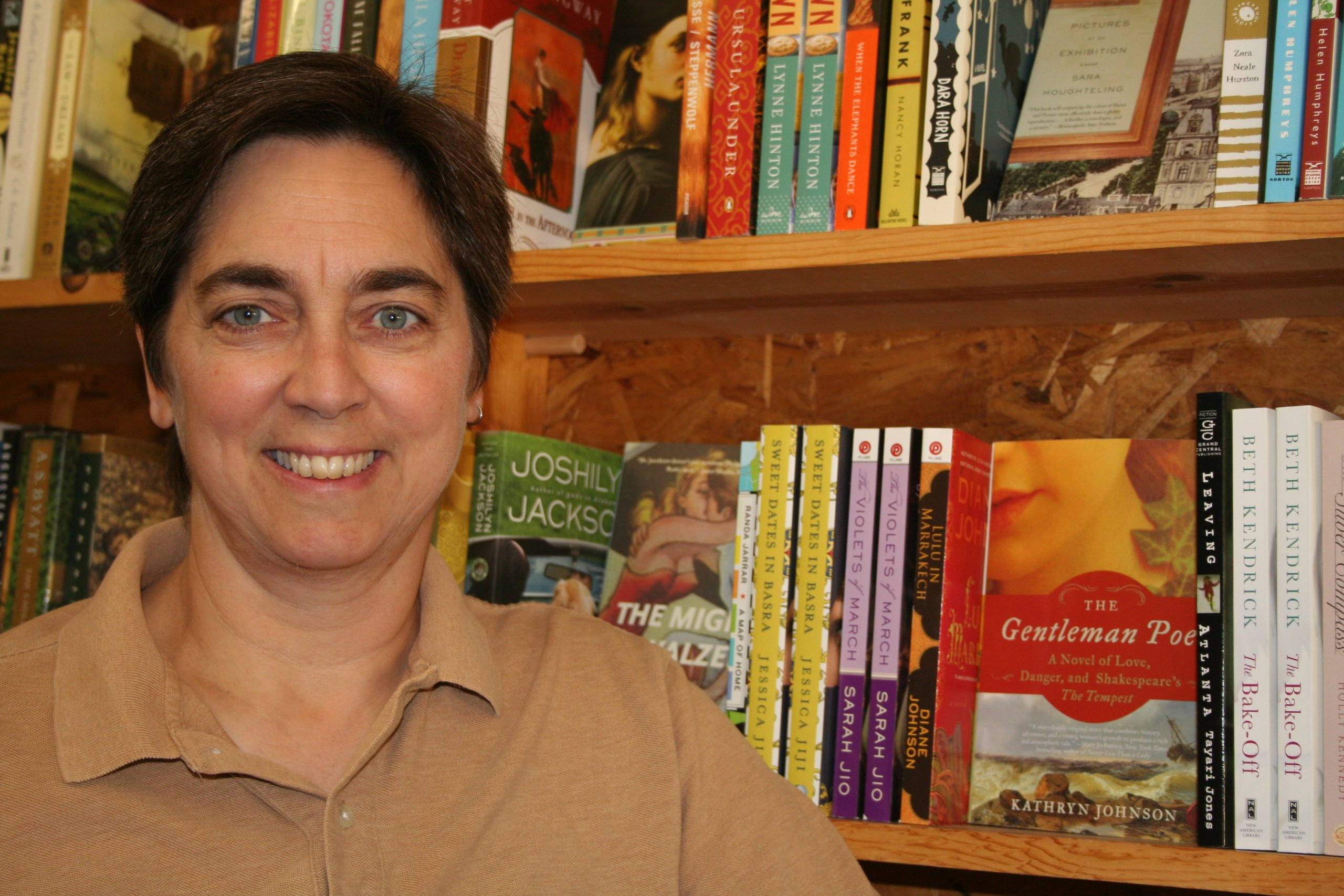 A woman with short brown hair stands in front of a shelf of books.