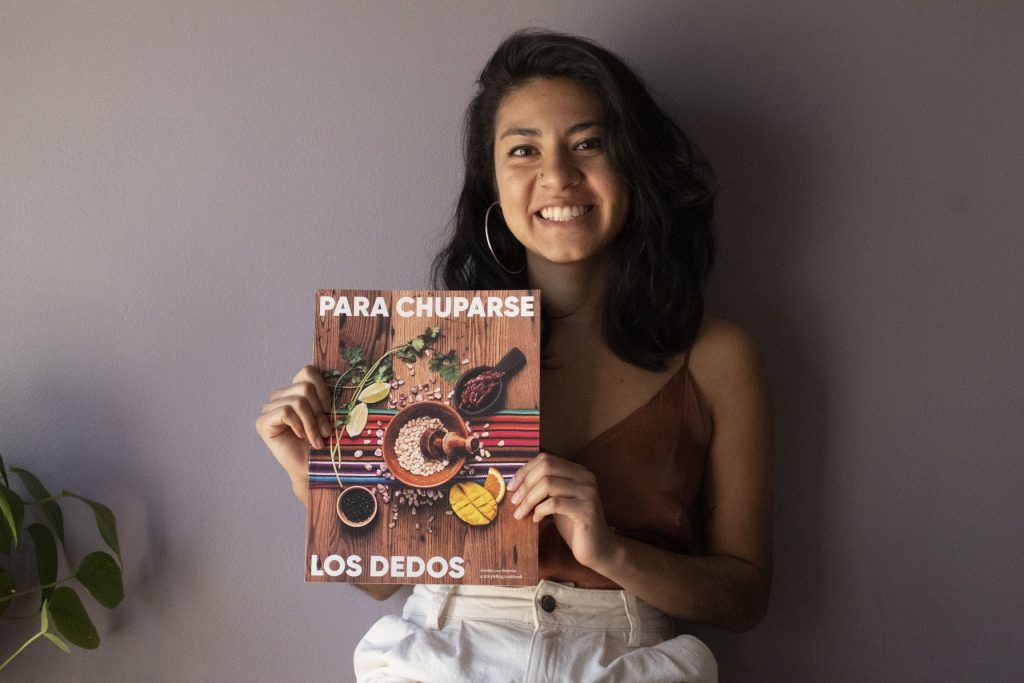 A smiling Latinx woman holds up a cookbook.