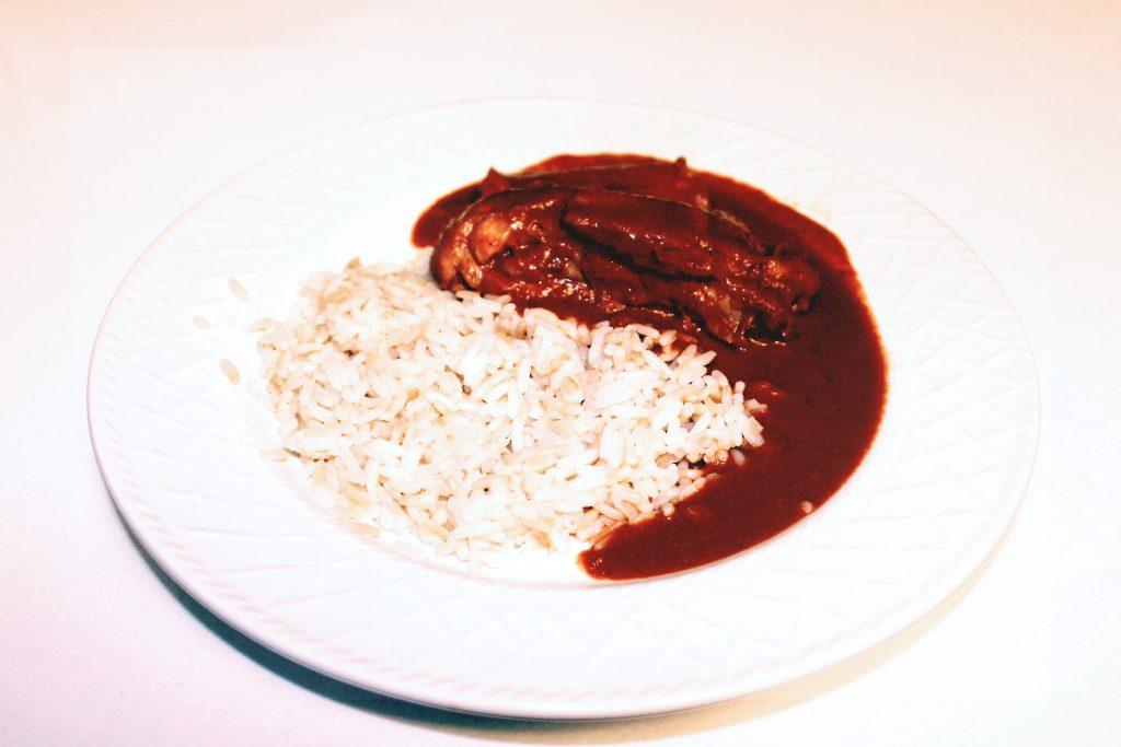 A white dish with half rice and half dark chocolate colored meat stew next to the rice.