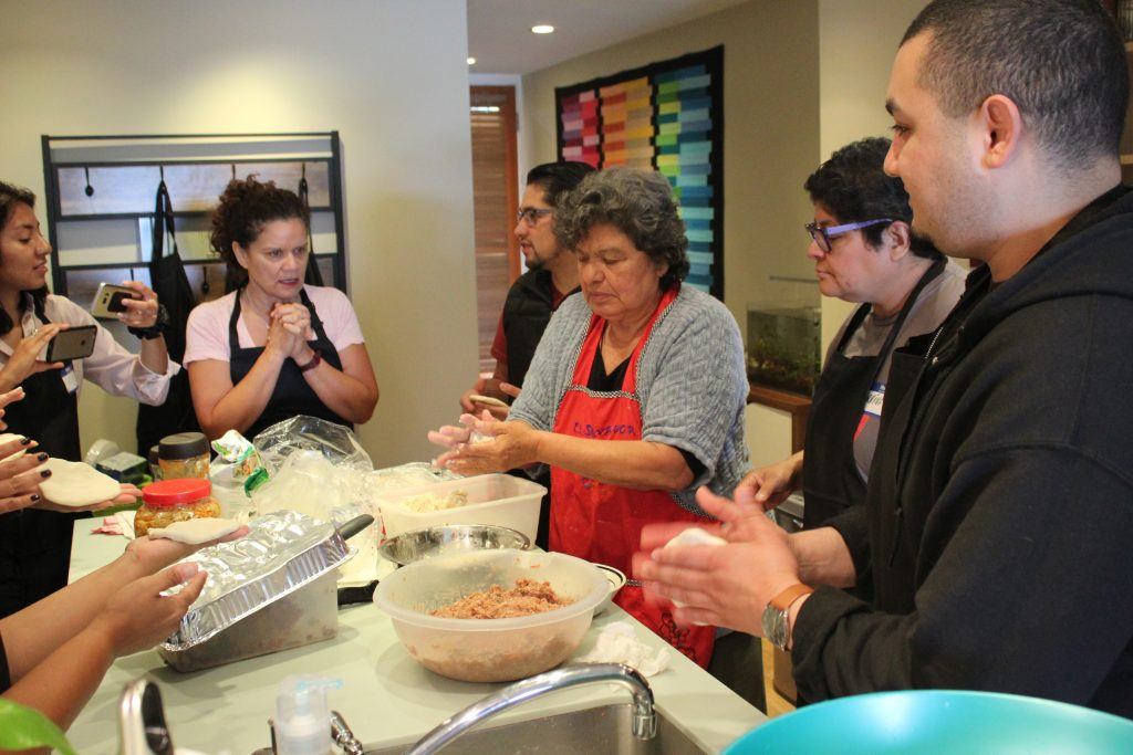 An image of several people gathered around a kitchen counter making pupusas by hand.