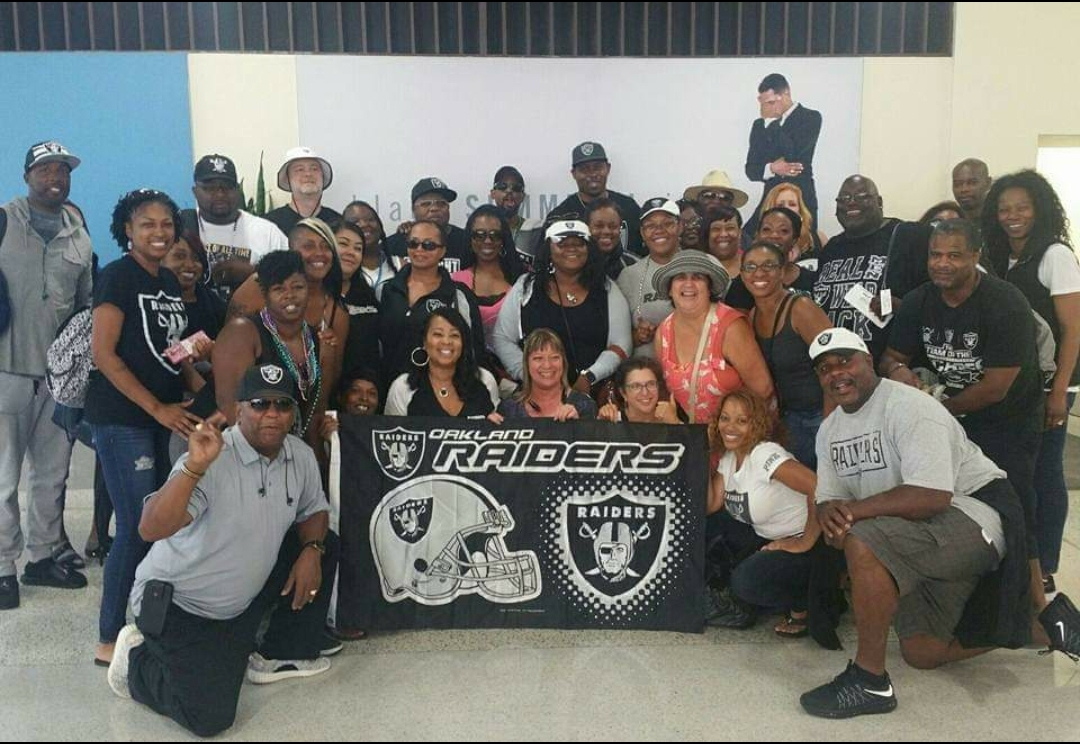 A large group of mostly African Americans pose with a Oakland Raiders banner