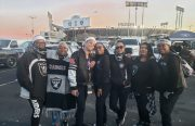 A group of women decked out in Oakland Raiders gear pose smiling in a photo in the parking lot.
