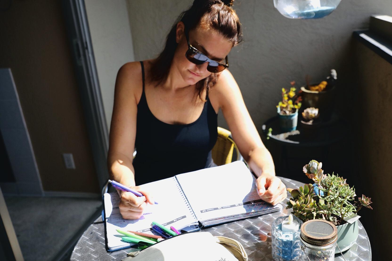A woman in sunglasses sitting outside has a planner open with pen in hand.
