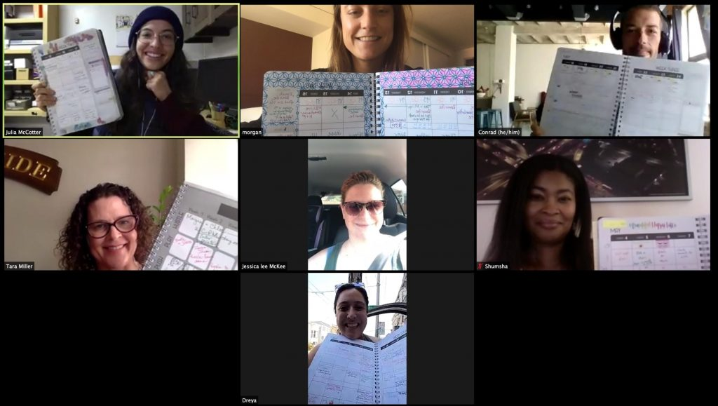 A screenshot of a diverse group of people holding up a planner/workbook during a Zoom.