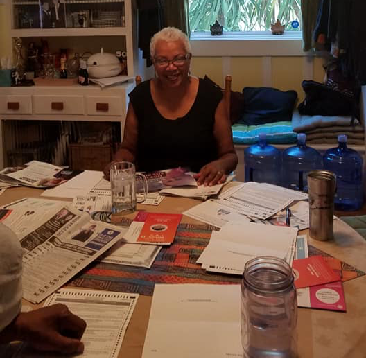 An African American woman with short grey hair sits at a table.