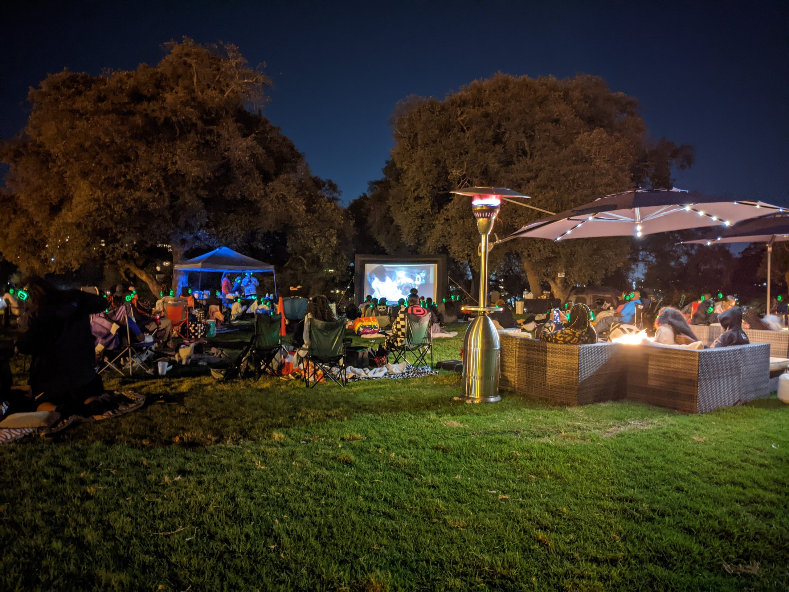 a night time scene at Lake Merritt, where people are watching a film outside.