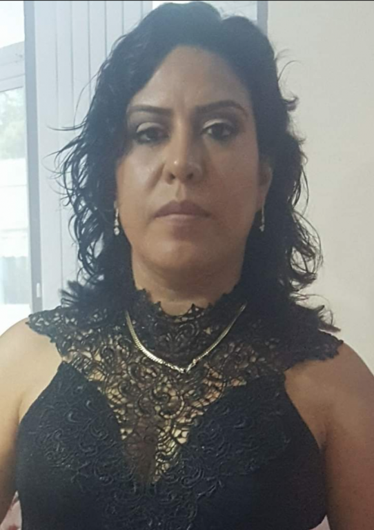 A photo of a Latina woman wearing a decorative black and gold top takes a selfie