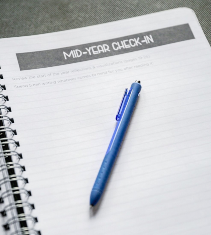 "An image of a notebook that says ""mid-year check-in"" at the top."