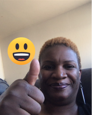 An African American woman with short hair smiles at camera with her thumbs up and a smile emoji on the screen.