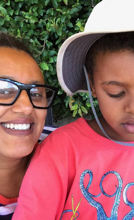 An African American woman with glasses is smiling, next to a young boy wearing a hat.