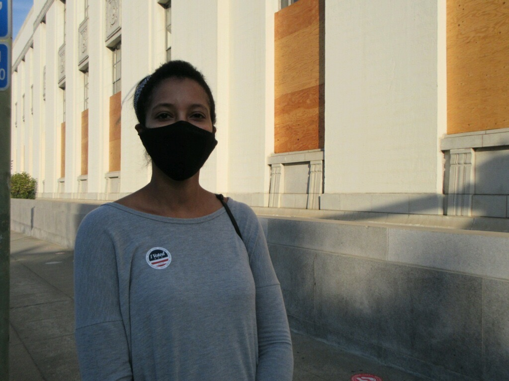 "A young woman wearing a mask stand in front of a building wearing an ""I voted"" sticker"