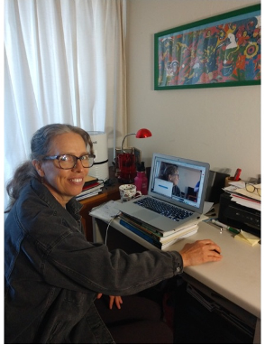 A woman wearing glasses and grey hair in a pony tail smiles for camera while sitting at desk.