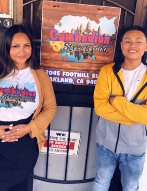 """An image of a Cambodian American woman in front of a sign that says """"Cambodian Street Food."""" A teen boy is smiling and standing next to the her and the sign."""