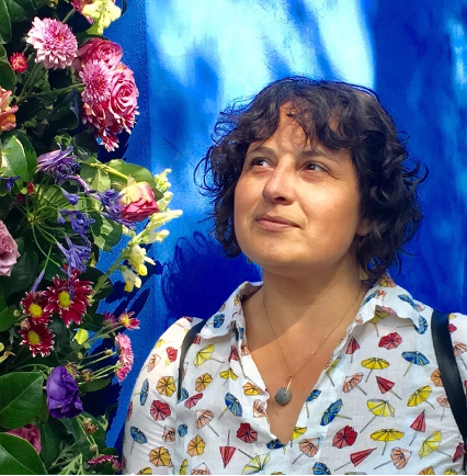 A woman with curly hair looks afar in front of a bright blue wall and flowers.