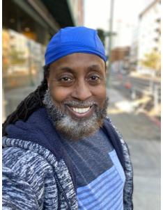 An African American man with a grey beard takes a selfie.