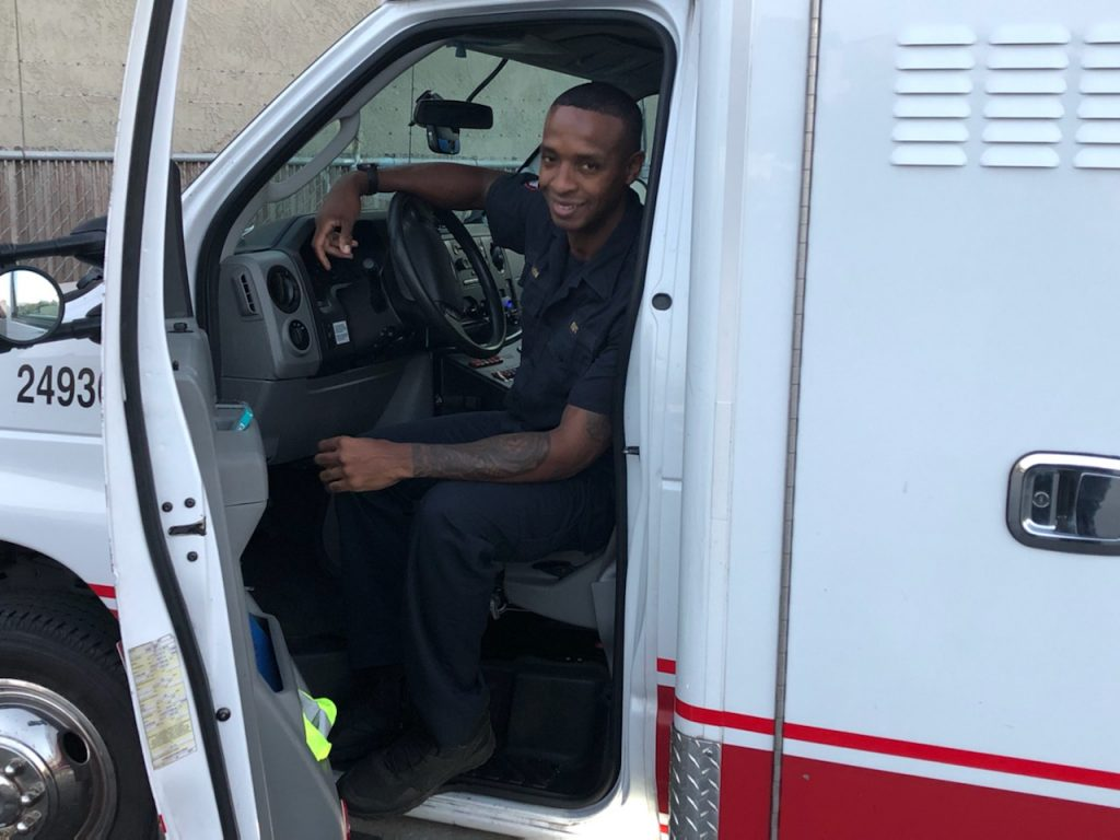 A young African American man sits in the driver's seat in an ambulance and smiles.