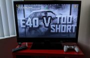 "An image of a large TV with ""E-40 V Too Short"" on the screen"