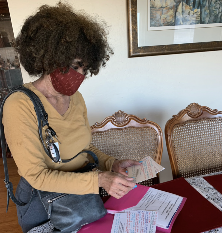 An African American woman wearing a face mask checks postcards.