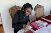 An African American woman puts stamps at the dining table.