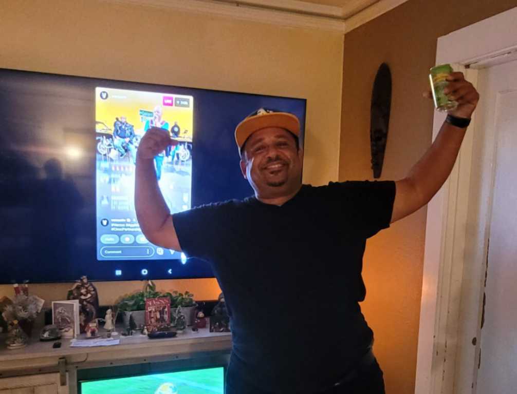 An image of a man wearing a baseball cap holding his arms up in triumph in front of a TV.
