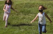 Two girls running on grass wearing black face masks.