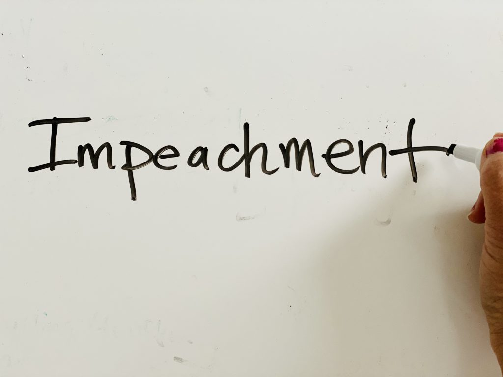 "the word ""impeachment"" written on a white board"