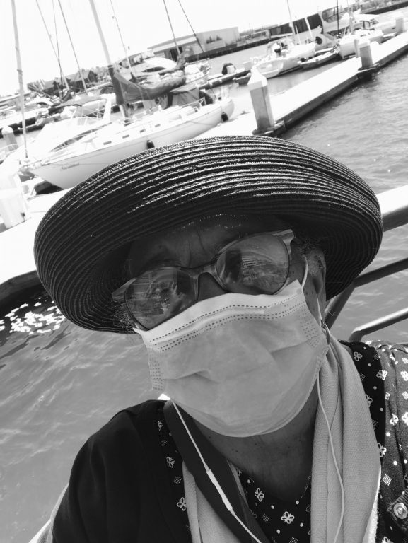 A black and white image of a woman wearing a hat, glasses, and a face mask standing outside by boat docks