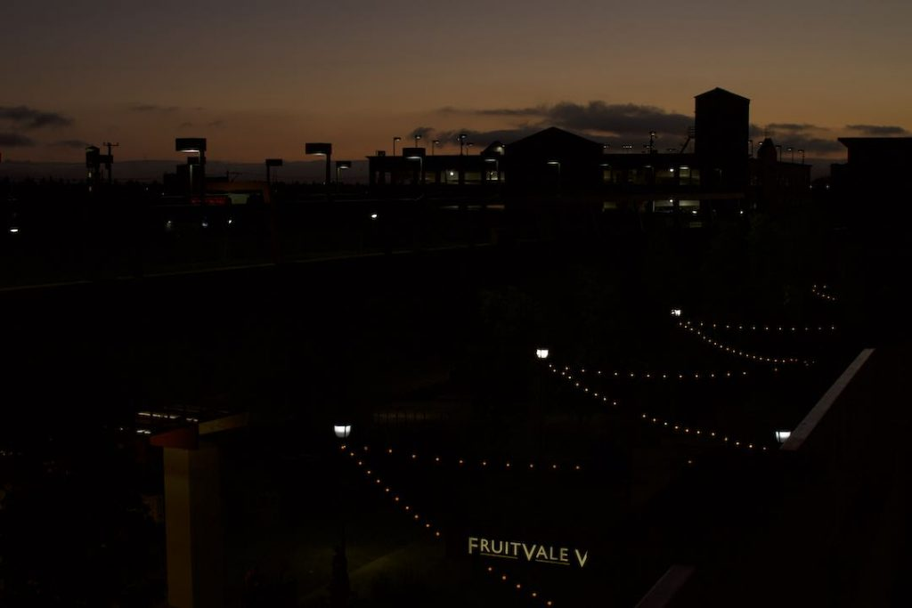 "An image of the night sky in Fruitvale, Oakland. All is dark except a few lights from the homes and ""Fruitvale"" sign."