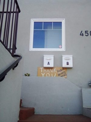 a grey stone house with a handwritten cardboard sign thanking postal workers