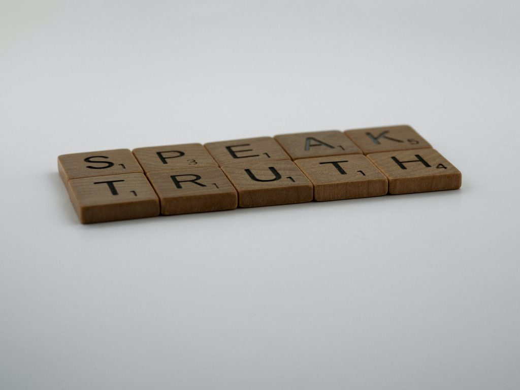 """Scrabble tiles against a white background that say """"Speak Truth"""""""