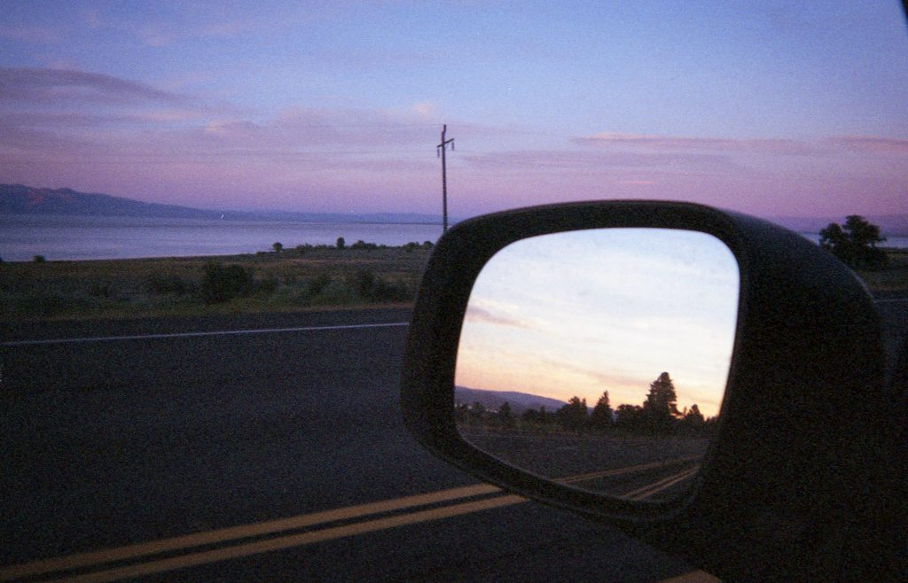 An image at dusk of a rearview mirror and pretty pink clouds.