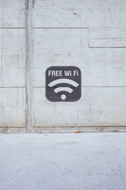 "a stencil painting that says ""free wifi"" against concrete backdrop."