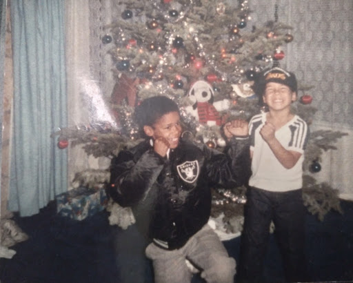 An image of two African American brothers play fighting in front of a Christmas tree and smiling, one wearing a tank top and the other a Raiders jacket.