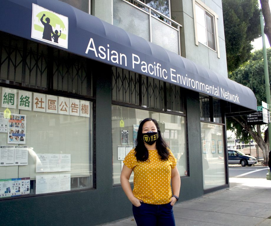 """A Chinese American woman stands in front of an awning that says """"Asian Pacific Environmental Network."""" Her facemark shows Asian and Black unity."""