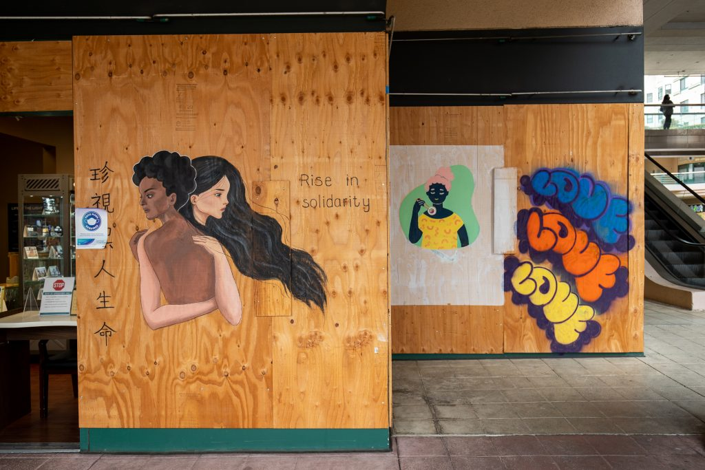 An image of a young Asian woman hugging a Black woman painted on wooden boards.