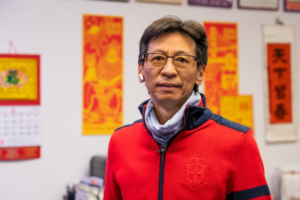 A Chinese American man stands in an office with bright new year banners in the back.