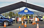 """Orange cones line the way in a parking lot at the Oakland Coliseum, where military dressed people point the way. A big blue tent that says """"Governor's Office of Emergency Services"""" is set up."""