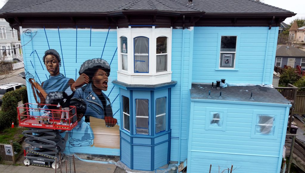 An image of a Victorian home painted with baby blue and images of powerful Black women from the Black Panther Party painted on the outside of the house in West Oakland.